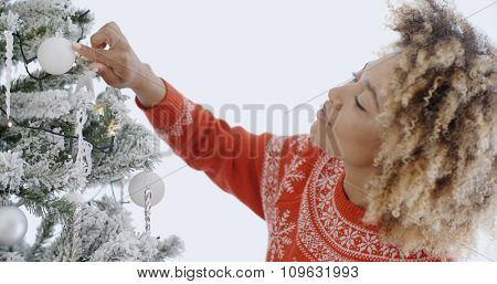 Attractive African woman decorating an Xmas tree with themed white and silver Christmas decorations stopping to admire a bauble