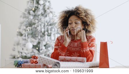 Young woman sitting at home wrapping gifts in front of the Christmas tree chatting on her mobile phone with her friends and family