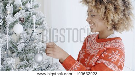 Happy trendy African girl with a cute afro hairstyle decorating a white and silver themed Christmas tree at Christmas