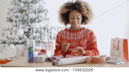 Happy young African woman wrapping presents at a table in her living room in front of the decorated Christmas tree