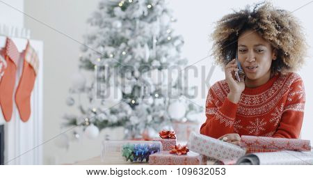 Young African woman wrapping gifts at Christmas sitting at a table in front of the Xmas tree chatting on her mobile phone  natural pre-occupied pose.