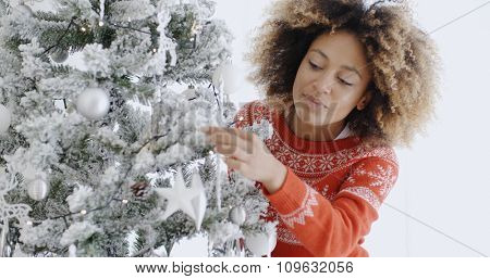 Attractive young African woman with a wild afro hairstyle preparing the tree for Christmas hanging decorations on the branches