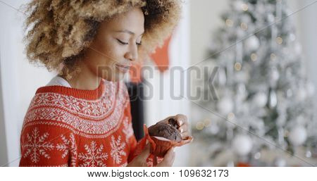 Young woman enjoying a Christmas treat sitting in front of a decorated tree in her house eating a freshly baked Xmas cake and smiling at the camera.
