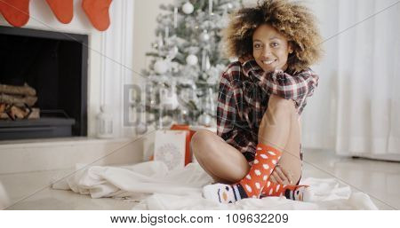 Smiling young woman in a Christmas living room sitting cross-legged in front of the tree alongside a decorated fireplace