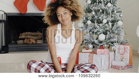 Smiling attractive young African American woman sitting cross-legged on the floor in front of the Christmas tree with its pile of decorative Xmas gifts