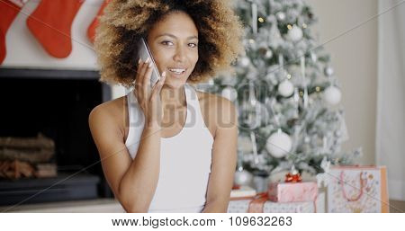 Young woman making a call at Christmas on her mobile phone to wish a family member a Merry Christmas as she stands in front of a decorated Xmas tree.
