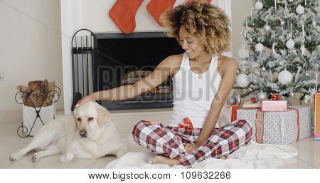 Attractive trendy young African woman celebrating Christmas with her dog sitting in front of the decorated fireplace and tree patting it on the head with a happy smile.