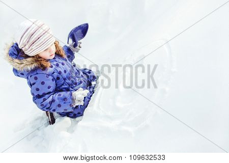 Little Girl Draws A Smiley Face On The Snow