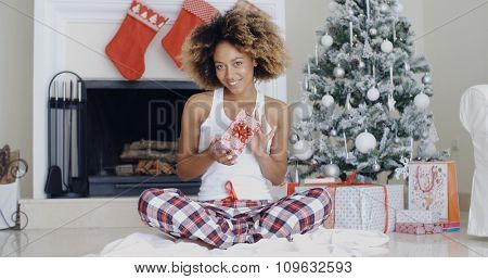 Pretty smiling young African American woman displaying a Christmas gift in her hands with a decorated tree and fireplace behind her