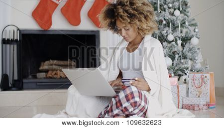 Young woman enjoying Christmas Eve sitting on the floor in front of a decorated Xmas tree in the living room using a laptop computer to maker online purchases.