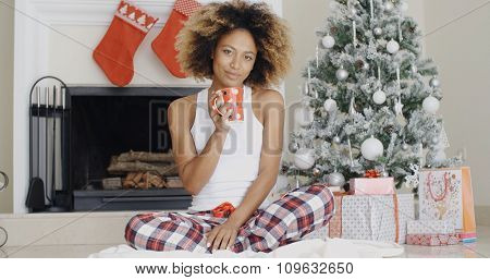 Smiling young woman enjoying a cup of Xmas coffee as she sits on the floor on front of the Christmas tree with its pile of gifts.