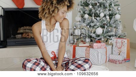 Young woman enjoying Christmas sitting cross-legged on the floor in front of the decorated tree eyeing the pile of decorative gift-wrapped  presents with a beaming smile.