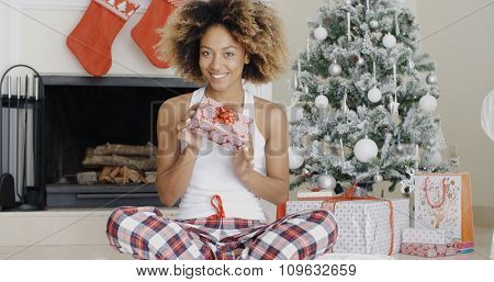 Happy young woman sitting cross-legged in front of the tree holding her Christmas gift with its decorative paper and bow up in the air with a beaming smile.