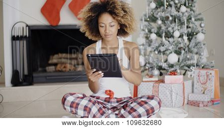 Trendy young African woman sitting on the floor in front of the Christmas tree attending to Xmas social media on her tablet-pc