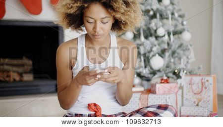Serious attractive young African woman checking for Christmas messages on her mobile phone as she sits in front of the decorated Xmas tree.