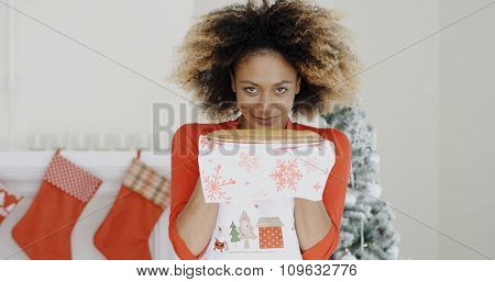 Happy young African woman holding a Christmas pastry in her hands with a smile of pleasure as she stands in front of the decorated fireplace