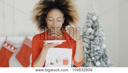 Young African cook with a freshly baked Christmas cake in her hand closing her eyes in bliss as she enjoys the aroma  Christmas tree background