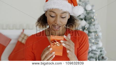 Excited young woman in a Santa hat looking at a decorative gift-wrapped Christmas gift in her hands with smiling anticipation