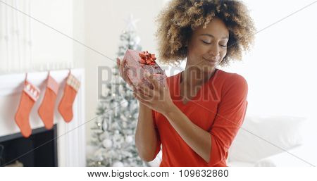 Blissful happy young woman holding up a Christmas gift in her hands as she tries to guess the contents in her decorated living room with tree.