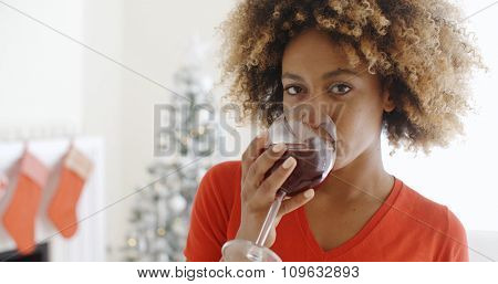 Attractive young African woman offering a Christmas toast as she raises a glass of red wine to the camera with a smile in front of a Christmas tree in her living room.