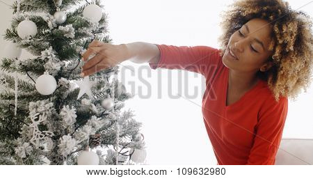 Pretty young African woman decorating her Christmas tree adding the last touches to the decorations as she adds a white star