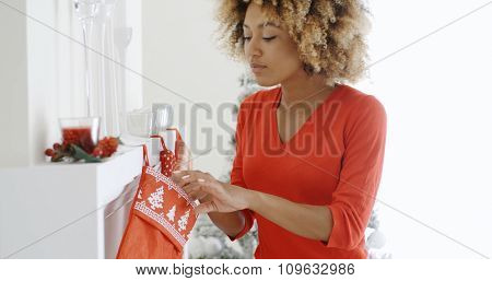 Happy young African American woman hanging colorful red Christmas stockings on the mantelpiece of her fireplace to celebrate the festive season