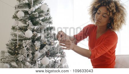 Attractive African woman with a wild curly afro hairdo decorating the Christmas tree with tinsel and ornaments to celebrate the festive season
