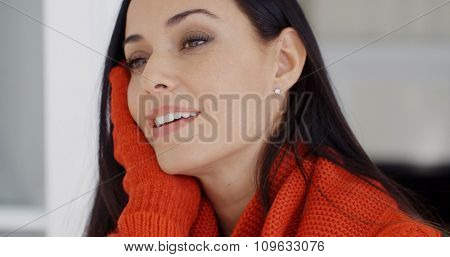 Pretty young woman with a gorgeous smile resting her head on her gloved hand as she smiles at the camera  close up portrait
