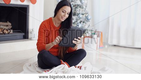Smiling woman catching up on her social media over the christmas holiday season as she sits on the floor in front of the Christmas tree using her tablet computer.