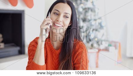 Young woman listening to a call on her mobile phone as she relaxes in front of the Christmas tree at home with a happy smile