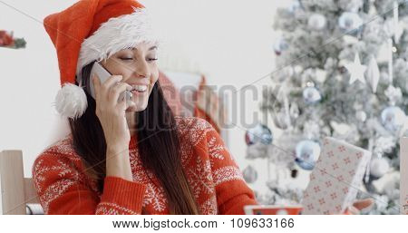 Young woman in a festive red Santa hat and sweater making a Christmas greeting call on her mobile phone listening to the conversation with a happy smile.