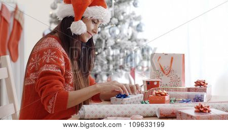 Attractive young woman in a festive red sweater and Santa hat sitting wrapping Christmas gifts in front of the tree