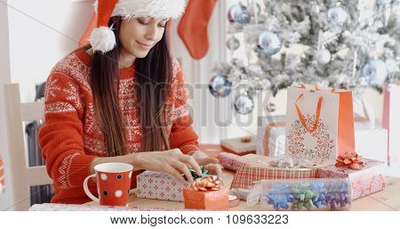 Young woman decorating her Christmas gifts with bows and ribbons as she sits at a table in front of a decorated Christmas tree