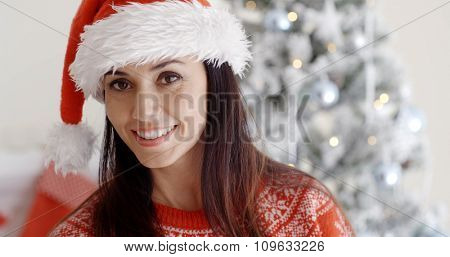 Smiling gorgeous young woman in a festive red Santa hat posing in front of a decorated Xmas tree  close up head and shoulders