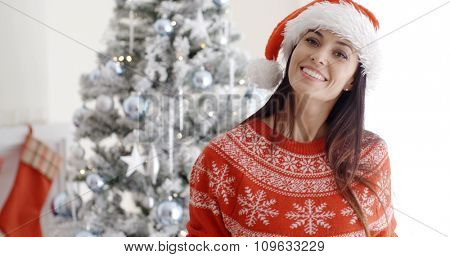 Happy smiling young woman in a festive red Santa hat and jumper standing in front of the Christmas giving the camera a warm friendly smile