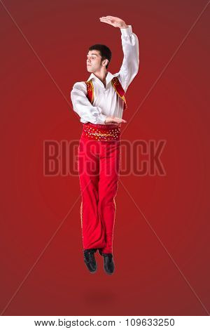 Jumping man wearing a toreador costume on red  in full length.