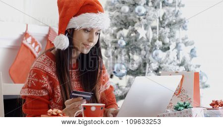 Young woman in a red Santa hat ordering Christmas gifts online sitting in front of the Xmas tree entering her bank card details on a laptop computer.