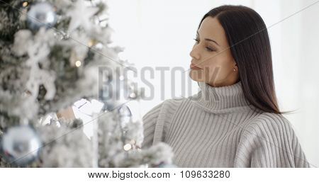 Pretty young woman with long brown hair standing decorating her white and silver themed Christmas tree with a smile of pleasure