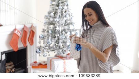 Pretty young woman opening a Christmas gift standing in front of the decorated tree holding the gift box in her hand as she unties the ribbon with a smile.