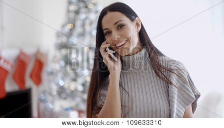 Young woman standing indoors at home in front of a Christmas chatting on her mobile phone with a happy smile