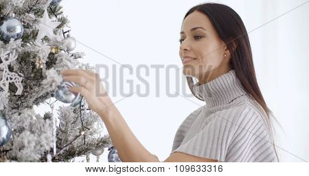 Stylish young woman admiring a decorated Christmas tree themed silver and white with a thoughtful smile  close up head and shoulders