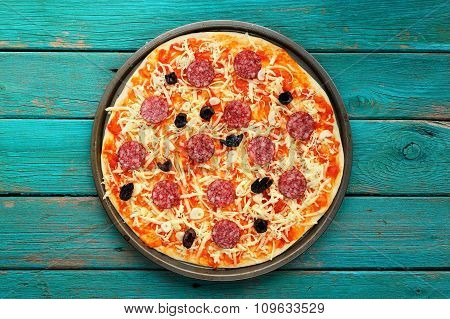 Uncooked Salami Pizza On Turquoise Background