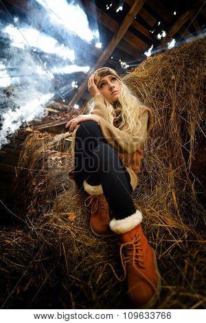 Beautiful woman relaxing in straw in smoky room