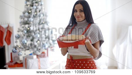 Young woman baking Christmas treats standing in her festive apron in front of the tree holding a freshly baked tart