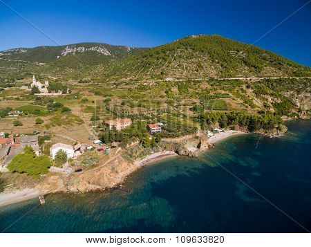 Aerial view of beach, Saint Nicholas Church and surrounding on Vis Island in Komiza town, Croatia.