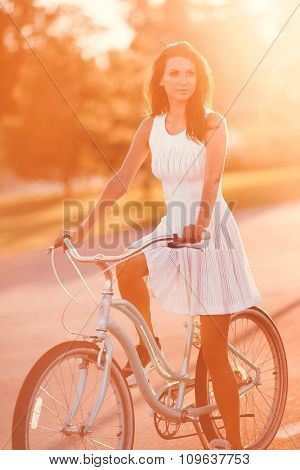 Beautiful brunette girl in white dress on bicycle at sunset in park
