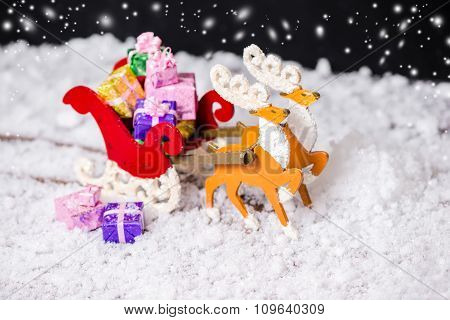 Composition Of Christmas Decoration Reindeer And Santa Sleigh With Gifts In Traces Snow On Black Bac