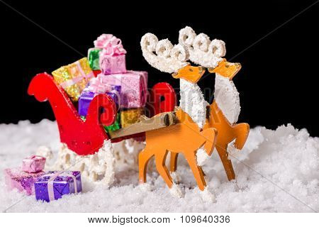 Still Life Of Christmas Decoration Reindeer And Santa Sleigh With Gifts In Snow Is Isolated On Black