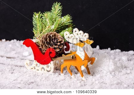 Composition Of Christmas Decoration Reindeer And Santa Sleigh With Branch Fir Tree, Pinecones In Tra