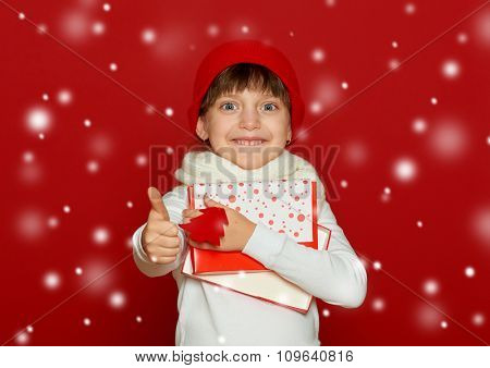 happy girl in santa hat with box gift show fir tree wool toy on red -winter, child,  christmas concept
